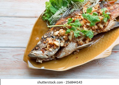 Thai style food main course: whole fried sea bass with garlic
