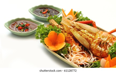 Thai style golden river prawn with garlic and pepper, served with exotic sauce on green plate and white background