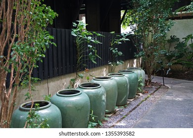 Thai style green glazed earthenware water jars by the pathway