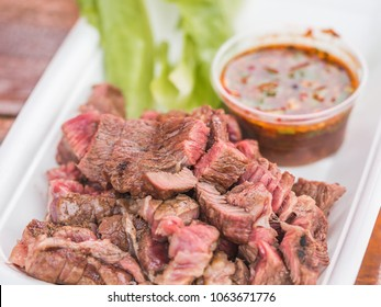 "Thai Style Grilled Beef with Isaan Spicy Dipping Sauce aka ""Crying Tiger Nam Jim Jaew"" Macro Closeup. Delicious Juicy Medium Rare Chunks of Barbecue Grilled Beef Steak as Gourmet Asian Food Background"