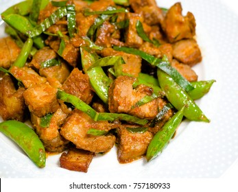 Thai style homemade Stir-fried crispy pork with red chili paste and Kaffir lime leaf with green pea.