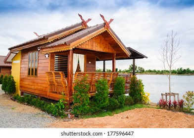 Thai style house with small tree near the pond