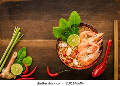Thai style noodle in bowl with spoon and chopsticks, Tom Yum Kung with Thai herbs, chilli, galangal, lime, lemongrass and kaffir lime leaf on wooden background.