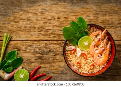 Thai style noodle in bowl, Tom Yum Kung with Thai herbs, chilli, galangal, lime, lemongrass and kaffir lime leaf on wooden background.