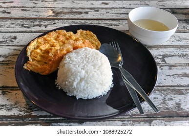 Thai style of simple omlet or fried egg with steamed white rice in black plate serve with clear soup on wooden table. Shot in isometric angle or man eye view.
