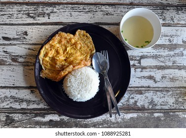 Thai style of simple omlet or fried egg with steamed white rice in black plate serve with clear soup on wooden table. Shot from above or bird eye view.