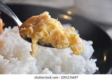 Thai style of simple omlet or fried egg with steamed white rice in a spoon of bite size ready to eat. Steamed white rice and black plate in background.