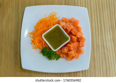 """Thai style spicy salmon dice salad named """"Yum"""" mixed vegetable and herb. Served with spicy sauce. Spicy Sashimi Salad Salmon . salmon and Thai spicy sauce with vegetable and herb in the bowl."""