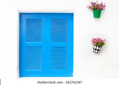thai style window. Blue on white wall with closed shutters