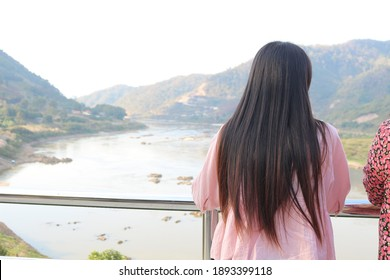 Thai teenage woman with long black hair Wearing a pink shirt, she is looking at the view of the Mekong River.