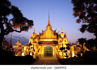 Thai temple with a golden glow and guarded by two huge statues. Shot with a view of blue evening sky in Bangkok, Thailand
