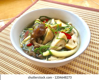 Thai three mushrooms and acacia leaf soup in white bowl white laid on small bamboo mat