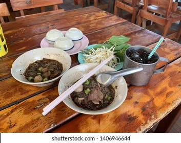 Thai traditional boat noodles with fresh vegetables side dise and thai style desserts on the wooden table. Local street food in Thailand.