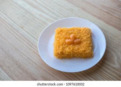 "thai traditional cusine dessert from yolk ,sweet coconut milk and  brown shugar call ""Cake foi thong"" serve on wood table."