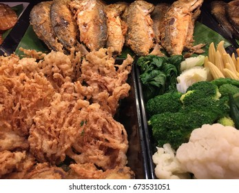Thai traditional food, crispy fried mackerel with local fried vegetables with flour and steamed vegetables always served with streamed rice.