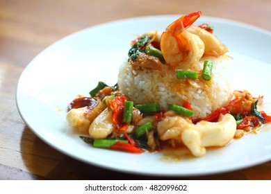 Thai traditional food : Khao Pad Kra Pao, Stir-fried sea food and basil leaves. Served with rice. (Selective Focus)