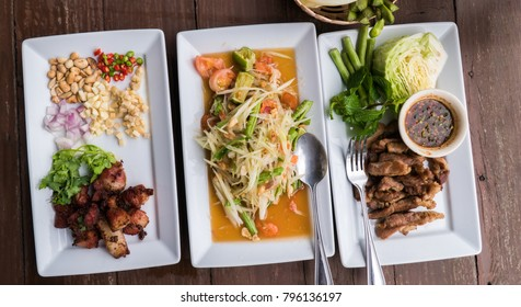 """Thai traditional food : with spicy papaya salad called """" Som Tam """" and fried pork"""