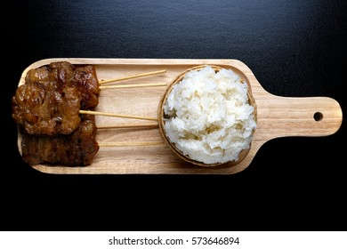 Thai Traditional Food,Pork grill on tray wood with sticky rice. black background (Thai Food)