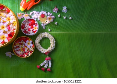 Thai traditional jasmine garland and Colorful flower in water bowls decorating and scented water, perfume, marly limestone, pipe gun on Banana leaf for Songkran Festival or Thai New Year.