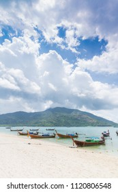 Thai traditional longtail boats on the white sand beach at Lipe Island, Thailand.