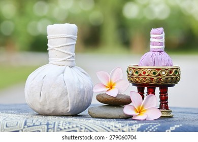 Thai traditional medicine. Body herbal ball, aromatherapy,pink yellow frangipani. Background is Blue Thai fabrics