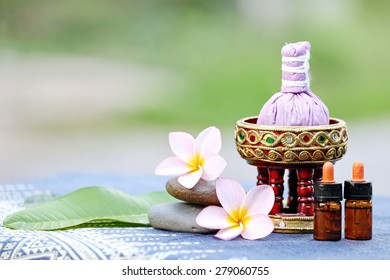 Thai traditional medicine. Body herbal ball, volatile oil,aromatherapy,pink yellow frangipani. Background is Blue Thai fabrics