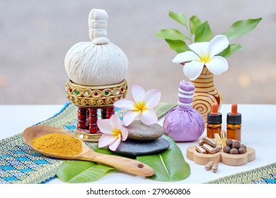Thai traditional medicine.yellow dry powder, ball lyrics, Herbal capsules, Body herbal ball, aromatherapy, pink yellow frangipani. The background is white cotton. Thailand blue striped drape the shawl