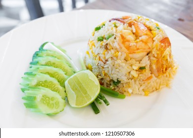 Thai traditional shrimp and egg fried rice served with sliced cucumber green onion and piece of lime on white ceramic dish