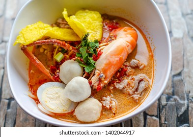 Thai traditional style noodle in seafood spicy soup well known as 'Kuayteaw Tomyam', with fresh shrimp and pork ball in white bowl