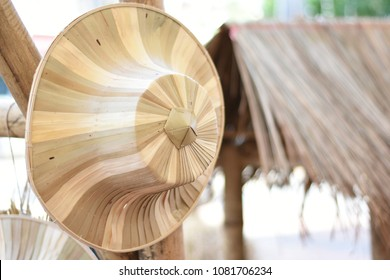 """Thai traditional weave hat or """"Ngob"""" basketry from natural materials hanging on the bamboo."""