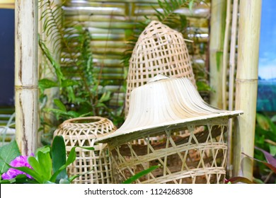 """Thai traditional weave hat or """"Ngob"""" basketry from natural materials placed on the basket work decorated in a garden."""