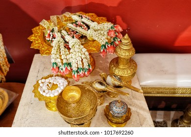 Thai Traditional wedding  ceremony accessories include fresh flowers steering for the bride and groom, packthread Mong Kol, two conch shell,  water recharqe all things place on gold tray color.