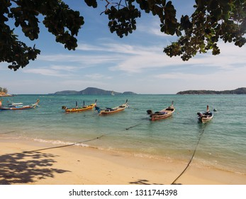 Thai traditional wooden longtail boat and beautiful sand beach. Thailand.