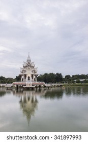 The thai white temple over water and blue sky