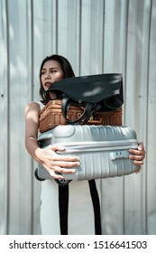Thai woman on whitedress carrying bags.