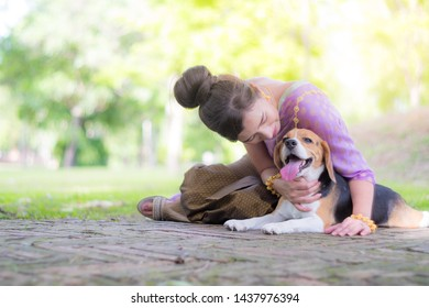 Thai Woman posing and wearing in Thai Ayutthaya Traditional costume with purple clothes,sitting with beagle dog on the ground with warm tone color.