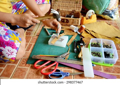 Thai woman punching hole and cutting for made handmade bag leather and key ring at home in Nonthaburi, Thailand.