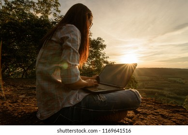 Thai woman using laptop working at top of mountain with sunrise background.