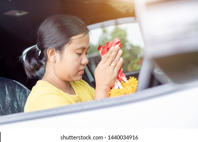 Thai woman with yellow flower garland in hand and praying in the new car for lucky, safety in Thai style