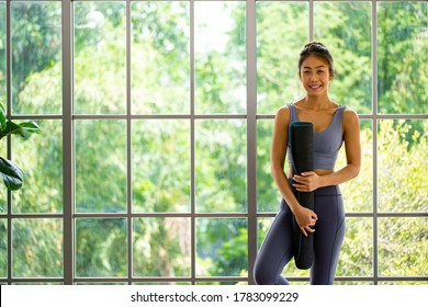Thai Frau Yoga.Asiatische Leute, die Yoga-Matte für Bewegung im Wohnzimmer halten.Fitness bleiben zu Hause.Portrait-Sitzung im Wohnzimmer.