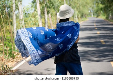 Thai women posing relax and playing indigo tie dye fabric shawl on the small street in countryside of Yasothon, Thailand