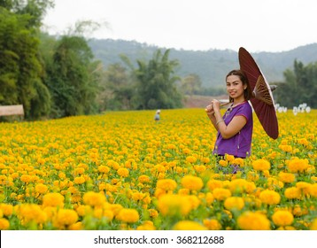 Thai women in traditional costume at a marigold field