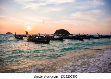 Thai wooden boat on sea beach with sunset at Lipe island, Satun province, Thailand