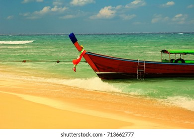 Thai wooden boat tied to the sandy shore of a deserted sandy beach for a romantic couple on a background of sea horizon