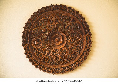 Thai wooden decoration. A rounded detailed plate, hanging on the wall.