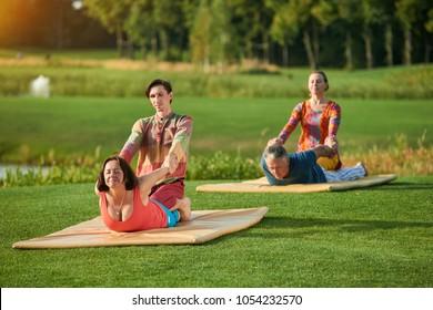 Thai yoga bodywork. Thai massage in cobra position. Group sport exercises outdoor.