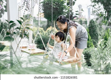 Thai young Asian mother and daughter play swing and both are very happy because spent together. Mum and little girl swinging on the swing.Great fun family parents motherhood mother day concept