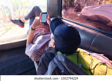 Thai young traveler lay down relax playing smartphone inside a van.