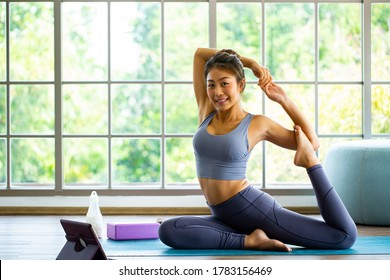 Thai young woman attractive smiling.Practic Young attractive smiling woman practice yoga.Asian poeple sitting in One Legged King Pigeon or  Eka Pada Rajakapotasana pose in living room.