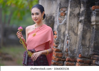 Thai young woman portrait in Thai traditional dress at historical park, there is a lotus in here han, Ayutthaya, Thailand.